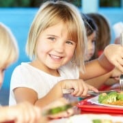 Elementary Kids Enjoying Healthy Lunch In Cafeteria